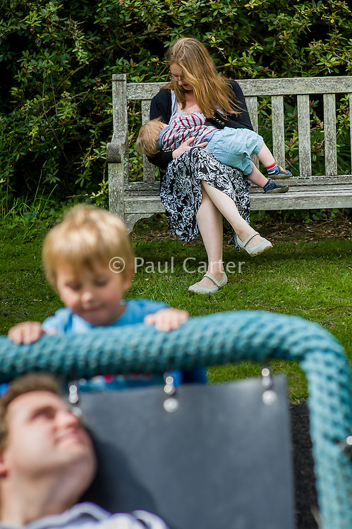 A mother  breastfeeding her child during a family outing to a local park and gardens. Her older boy is pushing her husband on a swing.<br /> <br /> 11-06-2015