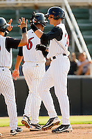 Trayce Thompson #24 of the Kannapolis Intimidators high fives teammate Carlos Sanchez #29 after hitting a 3-run home run in the bottom of the third inning against the Delmarva Shorebirds at Fieldcrest Cannon Stadium on August 7, 2011 in Kannapolis, North Carolina.  The Intimidators defeated the Shorebirds 8-3.   (Brian Westerholt / Four Seam Images)
