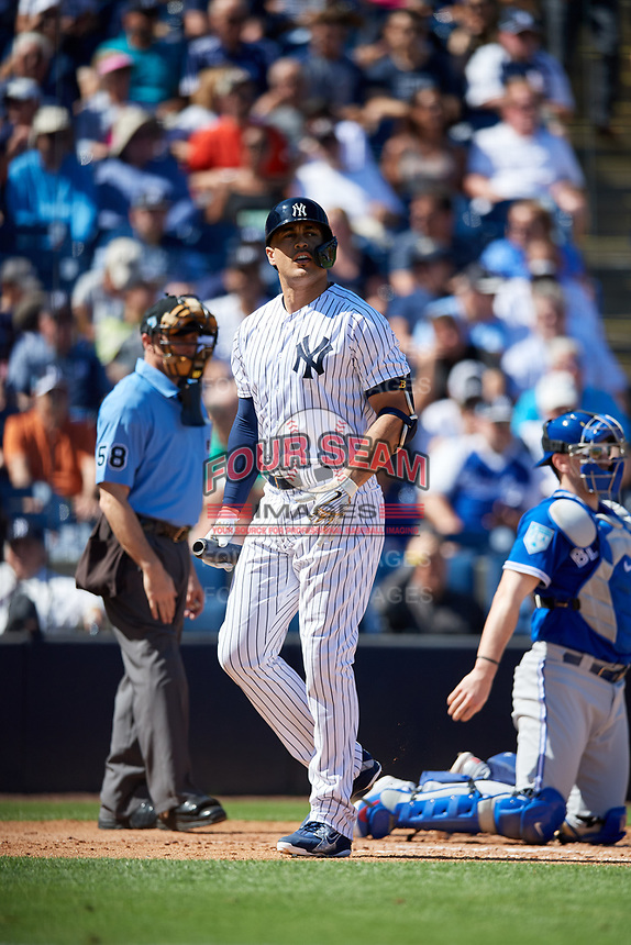 New York Yankees designated hitter Giancarlo Stanton (27) walks back to the dugout as home plate umpire Dan Iassogna and catcher Danny Jansen (9) look on during a Grapefruit League Spring Training game against the Toronto Blue Jays on February 25, 2019 at George M. Steinbrenner Field in Tampa, Florida.  Yankees defeated the Blue Jays 3-0.  (Mike Janes/Four Seam Images)