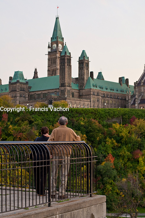A man and a woman look at the Parliament in Ottawa Monday September 27, 2010. Parliament Hill (colloquially The Hill, in French: Colline du Parlement) is an area of Crown land on the southern banks of the Ottawa River in downtown with a Gothic revival suite of buildings, the parliament buildings, that serves as the home of the Parliament of Canada and contains a number of architectural elements of national symbolic importance.<br /> <br /> PHOTO :  Francis Vachon - Agence Quebec Presse