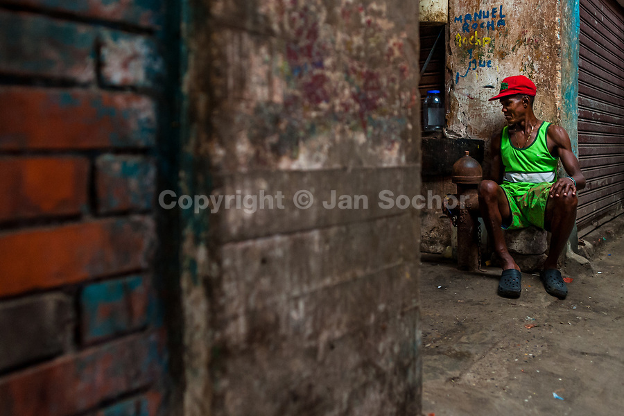 An Afro-Colombian carrier waits for customers inside the market of Bazurto in Cartagena, Colombia, 14 December 2017. Far from the touristy places in the walled city, a colorful, vibrant labyrinth of Cartagena's biggest open-air market sprawls to the Caribbean seashore. Here, in the dark and narrow alleys, full of scrappy stalls selling fruit, vegetables and herbs, meat and raw fish, with smelly garbage on the floor and loud reggaeton music in the air, the African roots of Colombia are manifested.