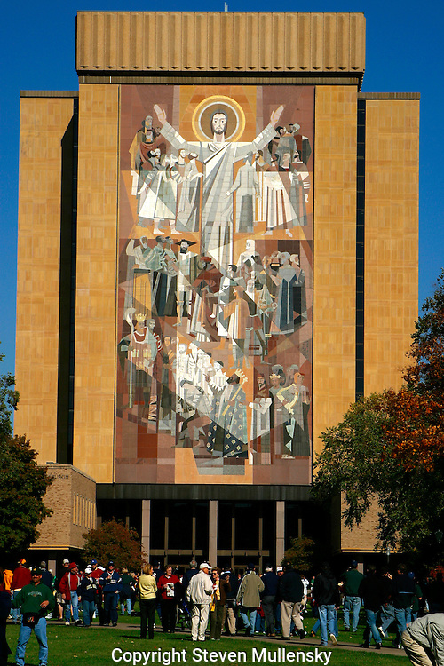 """Notre Dame Stadium is the home football stadium for the University of Notre Dame Fighting Irish football team. The stadium is located on the campus of the University of Notre Dame at Notre Dame, Indiana, just north of the city of South Bend, Indiana, USA..The stadium is known for its view of """"Touchdown Jesus"""", a nickname given to the large mural of the resurrected Jesus entitled """"the Word of Life"""" which is located on the Hesburgh Library, looming over the stadium mirroring the raised arms of a referee signifying a touchdown. Expanding the stadium has had the side-effect of partially obscuring the view of Touchdown Jesus from the field.."""