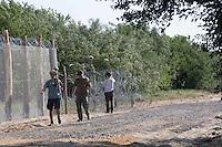 workers at the new wall on the border between Serbia and Hungary to stop immigrants coming from Syria and Afghanistan ; lavori di costruzione e controllo del nuovo muro al confine tra Serbia e Ungheria per fermare gli immigrati in arrivo da Siria e Afghanistan