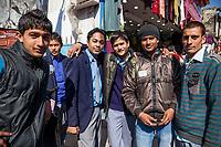 India, Dehradun.  Young Indian Men on a Busy Shopping Street.