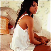 African American woman relaxing on bed<br />