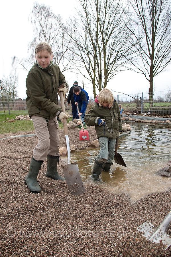 Grundschulklasse, Schulklasse legt einen Schulteich, Schul-Teich, Teich, Gartenteich, Garten-Teich im Schulgarten an, Kinder verteilen feinkörnigen Kies im Teich, der als Bodensubstrat für den neuangelegten Teich dient