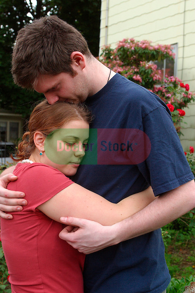 teenage boy and girl hugging while walking in suburban neighborhood, young love