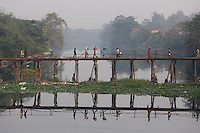 People walk across a bridge above a river on the outskirts of Kolkata.<br /> <br /> To license this image, please contact the National Geographic Creative Collection:<br /> <br /> Image ID: 1925817 <br />  <br /> Email: natgeocreative@ngs.org<br /> <br /> Telephone: 202 857 7537 / Toll Free 800 434 2244<br /> <br /> National Geographic Creative<br /> 1145 17th St NW, Washington DC 20036