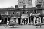 China, Shanghai.  High-density, high-rise blocks tower over traditional-style Shanghai housing which will soon be demolished. 2000s.