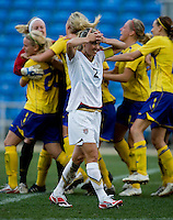 USWNT defender (2) Heather Mitts walks back to midfield after she missed a penalty kick as the Swedish team celebrate in the background after the Algarve Cup final at the Estadio Algarve in Faro, Portual.  The USWNT lost to Sweden on penalty kicks after it was tied in regulation at 1-1.