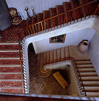 The cantilevered staircase has a wooden balustrade and terracotta tiled steps