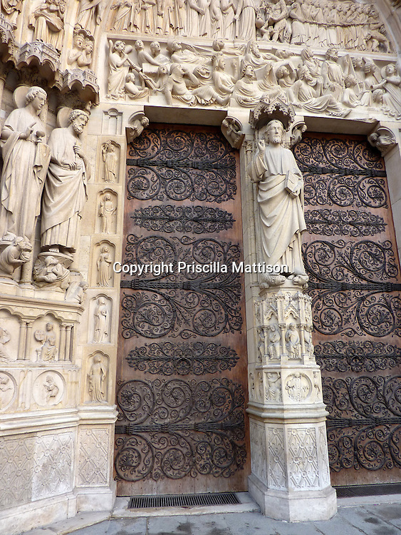 Paris, France - February 2, 2011:  Stone carving and ornate doors mark an entrance at Notre Dame Cathedral.