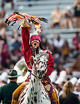 Florida State mascot Osceola atop Renegade leads the football team onto the field