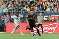 FOXBOROUGH, MA - AUGUST 4: Eduard Atuesta #20 of Los Angeles FC dribbles at midfield as Luis Caicedo #27 of New England Revolution defends during a game between Los Angeles FC and New England Revolution at Gillette Stadium on August 3, 2019 in Foxborough, Massachusetts.