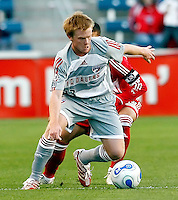 FC Dallas midfielder Dax McCarty (13) tries to get away from Chicago Fire midfielder Chris Armas (14).  FC Dallas defeated the Chicago Fire 2-1 at Toyota Park in Bridgeview, IL on May 17, 2007.