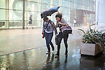 © Joel Goodman - 07973 332324 .  13/09/2016 . Salford , UK . A thunderstorm breaks a day of hot weather , sending people running with umbrellas at Salford Quays in Greater Manchester . Photo credit : Joel Goodman