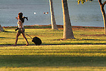 A photographer scouts out a location to take a photograph on Magic Island, Oahu, Hawaii.