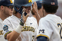 Michigan Wolverines outfielder Jesse Franklin (7) celebrates after scoring during Game 1 of the NCAA College World Series against the Texas Tech Red Raiders on June 15, 2019 at TD Ameritrade Park in Omaha, Nebraska. Michigan defeated Texas Tech 5-3. (Andrew Woolley/Four Seam Images)