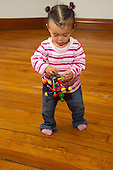 MR / Schenectady, NY. Infant in early walking stage (girl, 12 months, African American & Caucasian) exhibits 12-month-old human development milestone behavior as she walks while carrying a toy. MR: Dal4. ID: AL-HD. © Ellen B. Senisi