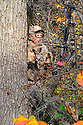 00105-052.11 Bowhunting: A well camouflaged archer is rattling antlers to attract a buck during fall.  Hunt, call, rut.