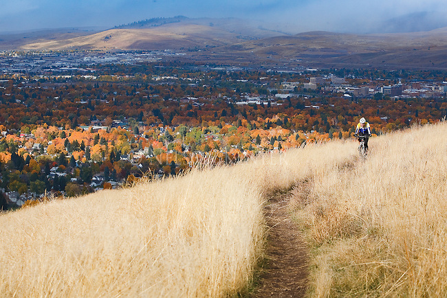 A mountain bike rider rides up a trail on Mount Sentinel in Missoula, Montana. The autumn colors of the valley trees are spot lighted by the sun.