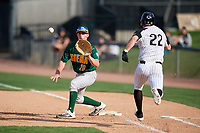 Siena Saints first baseman Eddie Sweeney (20) stretches for a throw as Chandler Robertson (22) runs up the base line during a game against the UCF Knights on February 17, 2019 at John Euliano Park in Orlando, Florida.  UCF defeated Siena 7-1.  (Mike Janes/Four Seam Images)