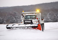 A driver removes snow Wednesday, Feb. 17, 2021, from in front of a row of hangars at pushes it to the fence at Drake Field at the Fayetteville Executive Airport. A winter storm dumped several more inches of snow requiring crews to plow again at the facility. Visit nwaonline.com/210218Daily/ for today's photo gallery. <br /> (NWA Democrat-Gazette/Andy Shupe)