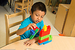Education Preschool 4-5 year olds boy talking and playing using colorful construction as a vehicle or play piece, talking to himself