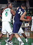 Jackson State Tigers forward Grant Maxey (32) passes around North Texas Mean Green forward George Odufuwa (4)  in the game between the Jackson State Tigers and the University of North Texas Mean Green at the North Texas Coliseum,the Super Pit, in Denton, Texas. UNT defeated Jackson 68 to 49