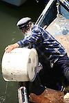 whiskered old man in panga boat empties water into harbor. Ensenada, Baja California. Mexico
