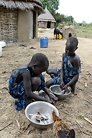 THIOPIA, Gambela, region Itang, Nuer village Pilual, twin sisters / AETHIOPIEN, Gambela, Region Itang, Dorf Pilual der Ethnie NUER, Hof von Herr Mun Kunen und Frau Neelam , sie sind vor dem Buergerkrieg aus dem Suedudan gefluechtet, Bhan ´s Schwestern sind Zwillinge, waschen Geschirr