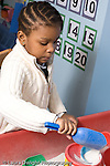 Educaton preschool 4-5 year olds girl playing at sand table vertical
