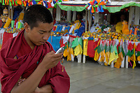 Traditional Buddist Monk, meets the new way, cellphones have arrived in Tibet, near the Jokhang Temple,.The Jokhang Temple is one of Tibet's holiest shrines, originally built in 647 A.D. in celebration of the marriage of the Tang Princess Wencheng and the Tubo King Songtsen Gampo. In front of the gate is a stone Tablet of Unity from the Tang Dynasty; inscribed are both Chinese characters and Tibetan script. Nearby is the stump of the willow tree said to have been planted by Princess Wencheng herself; two younger willow trees now flank the stump of the first tree...Located in the center of old Lhasa, the temple was built by craftsmen from Tibet, China, and Nepal and thus features different architectural styles. The temple is also the spiritual center of Tibet and the holiest destination for all Tibetan Buddhist pilgrims. In the central hall is the Jokhang's oldest and most precious object--a gold statue of a seated 12-year-old Sakyamuni. This is said to have been transported to Tibet by Princess Wencheng from her home in Changan in 700 A.D. Other precious antiques in the temple include a silk portrait of Buddha from the Tang Dynasty and a pearl gown and gold lamp from the Ming Dynasty. The three-leafed roof of the Jokhang offers splendid views of the bustling Barkhor market and across to the Potala Palace..