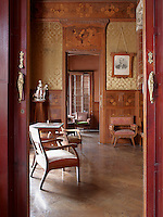 A framed portrait of Joaquin Navas, the original owner of the house, hangs on the wall of the living room, which is lined with marquetry panelling