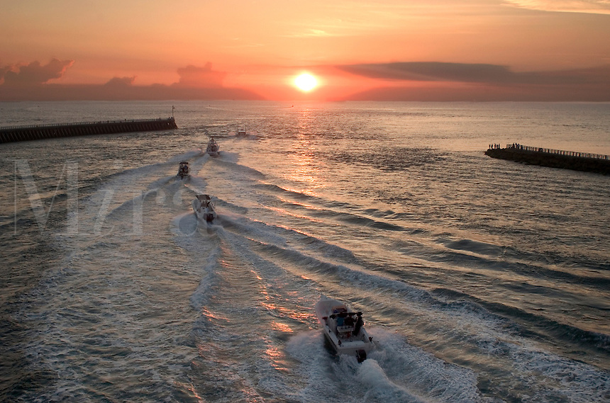 A line of fishing boats leave Sebastian Inlet on their way from Florida's Indian River to the Atlantic Ocean in the morning at sunris