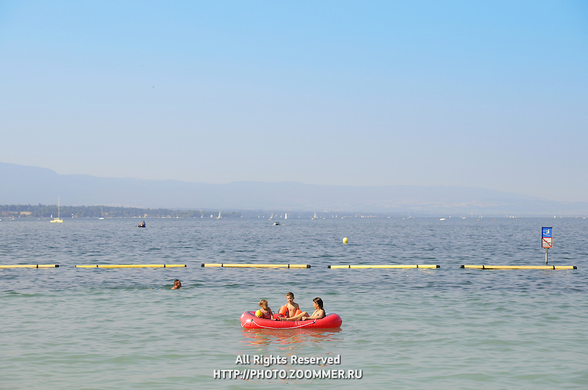 Kids swim on inflatable boat in Geneva lake with beautiful mountains landscape