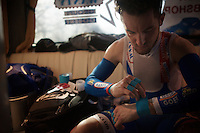 "Tim De Troyer (BEL/Wanty-Groupe Gobert) prepping himself ahead of the race in the teambus. <br /> The almost 53km's of riding over cobbles is so hard for the body that riders need to tape wrists and fingers to protect them. Most riders also have an extra layer of bartape on their handlebars to ""soften"" the impact of the cobbles.<br /> <br /> 113th Paris-Roubaix 2015"