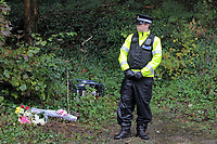 Pictured: A police officer stands by flowers and tributes left near the crime scene. Tuesday 26 October 2010<br /> Re: South Wales Police are investigating the murder of fifteen year old Rebecca Aylward from Maesteg, whose body was discovered in woods in Aberkenfig near Bridgend south Wales. Two fifteen year old men have been arrested and are being questioned by police.