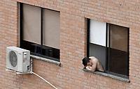 CALI - COLOMBIA, 07-04-2020: Un hombre se asoma en su ventana en Cali durante el día 15 de la cuarentena total en el territorio colombiano causada por la pandemia  del Coronavirus, COVID-19. / A man looks out from his window in Cali during the day 15 of total quarantine in Colombian territory caused by the Coronavirus pandemic, COVID-19. Photo: VizzorImage / Gabriel Aponte / Staff