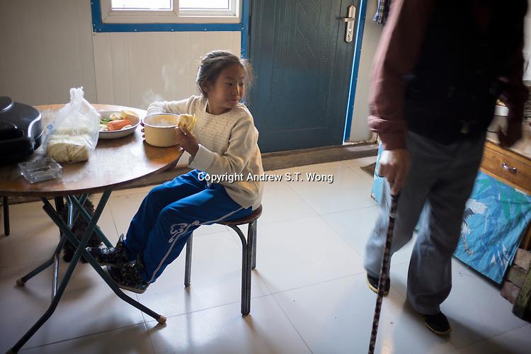 Granddaughter Dula of herder Renqima eats breakfast before going to school in Damao Banner, Inner Mongolia, China, October 2014.