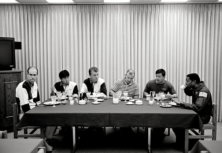 Image copyright John Angerson. <br /> STS-72 mission training.<br /> Tense moments of nerves and apprehension during pre-launch breakfast in the astronaut quarters. Commander Brian Duffy, Pilot Brent W. Jett, Mission Specialists Leroy Chiao, Daniel T. Barry, Winston E. Scott, and Koichi Wakata.<br /> Kennedy Space Centre, Florida, USA.