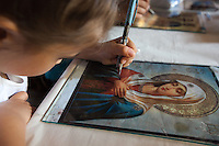 """Romania. Iași County. Iasi. A girl is painting a representation of the Blessed Virgin Mary on a glass <br /> in the Orthodox Church """"Saint Nektarios"""". Mary, also known as Saint Mary or the Blessed Virgin Mary, is identified in the Bible as the mother of Jesus. Iași (also referred to as Iasi, Jassy or Iassy) is the largest city in eastern Romania and the seat of Iași County. Located in the Moldavia region, Iași has traditionally been one of the leading centres of Romanian social, cultural, and artistic life. The city was the capital of the Principality of Moldavia from 1564 to 1859, then of the United Principalities from 1859 to 1862, and the capital of Romania from 1916 to 1918. 6.06.15 © 2015 Didier Ruef"""