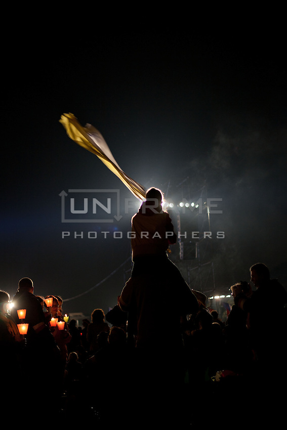 Pilgrims hold candles and another waves a flag during an evening vigil ahead of the beatification of Pope John Paul ll.