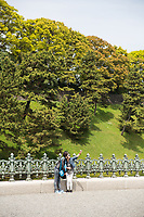 Tourists taking photos at the Imperial Palace in Tokyo.