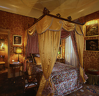 Sumptuous rich red and gold damask and deep yellow silk have been used to create the opulence of a boudoir in the atelier's guest bedroom