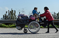Pictured: A female migrant, carrying all her belongings and her two young children in a wheelchair, walks on the motorway to get to Idomeni, Greece Wednesday 02 March 2016<br /> Re: More migrants have been arriving at the Greek FYRO Macedonian border of Idomeni, Greece.