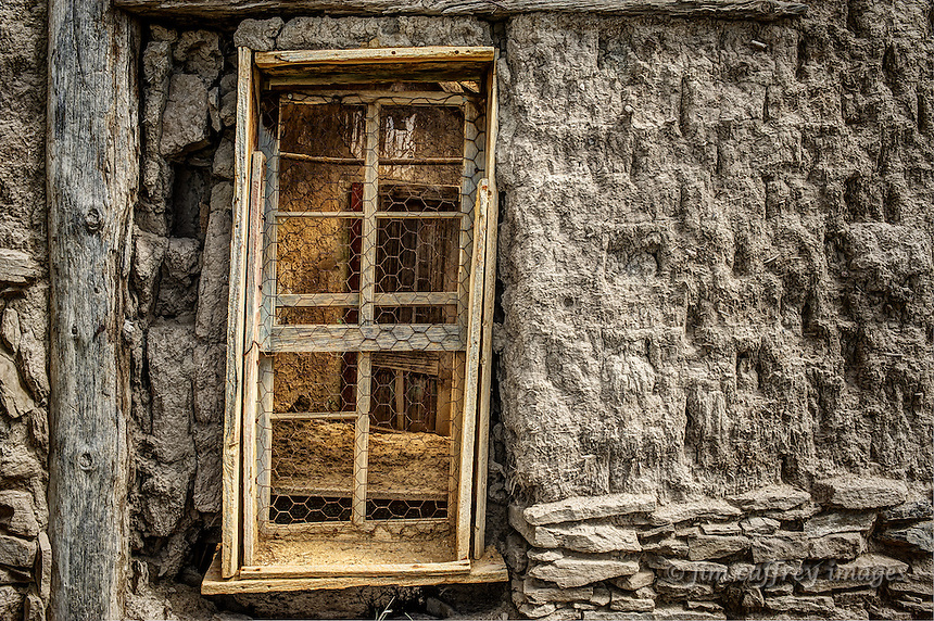 A sepia toned image of an adobe ruin witha window (in color) looking inside one of the rooms.