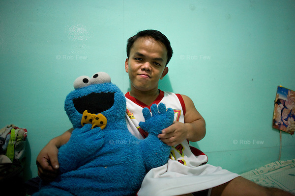 This is Alvin, pictured at home with his favourite Sesame Street character. Like several of his midget wrestling friends, he has a degree in computer engineering, but he can't get an office job because companies have height restrictions that apply to all employees irrespective of the nature of their job.<br /> <br /> In the red light area of Manila's Makati district, customers who've had enough of dancing girls have another form of exploitation to amuse them: midget oil wrestling.
