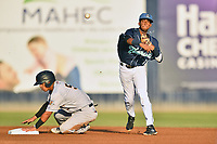 Asheville Tourists shortstop Cristopher Navarro (11) throws over Oswald Peraza (5) to complete a double play during a game against the Charleston RiverDogs at McCormick Field on August 15, 2019 in Asheville, North Carolina. The Tourists defeated the RiverDogs 6-3. (Tony Farlow/Four Seam Images)