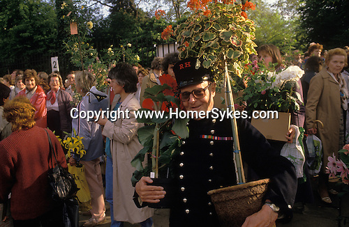 The Chelsea Flower Show. A Chelsea pensioner in his traditional costume, at the last days buys  flowers. On the last day the displays are sold off very cheaply.   London 1980s.<br /> <br /> Taken for my book The English Season published by Pavilion Books 1987